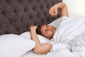 Male teacher waking up after only six hours of sleep