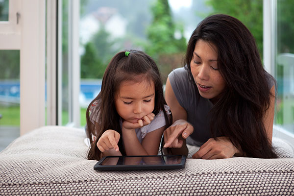 Mother and child learning on a tablet to prevent the summer slide