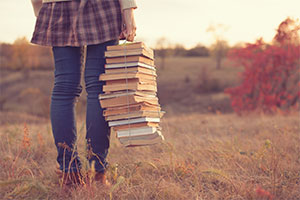 Bookbuzz – a girl holds a stack of books in a field