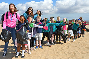 Primary school children and staff cleaning up local beach