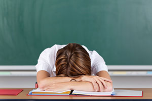 Stressed teacher with head on desk after working long hours