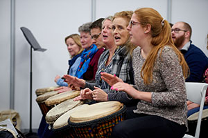 Women banging drums at the Music & Drama Education Expo