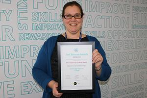 Sarah from Cambridge Regional College holding AoC Beacon Standard certificate