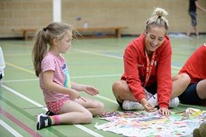children in sports hall with staff to support key workers