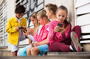 Group of children on their phones not worrying about cybercriminals