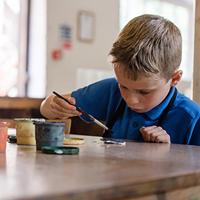 young boy in an Ironbridge Museum taking part in ceramic painting activities